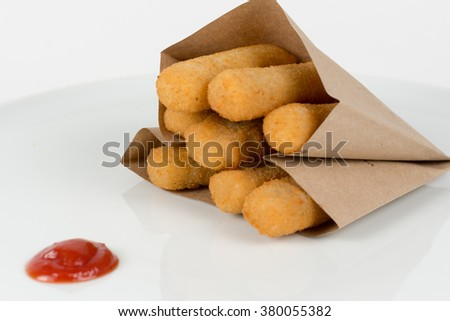 Fried potato croquettes in a paper bag with ketchup isolated on white