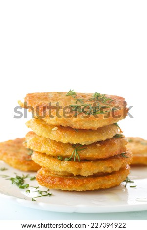 fried potato pancakes with dill on white background - stock photo