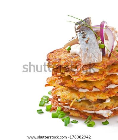 Fried potato pancakes with herring on white background - stock photo