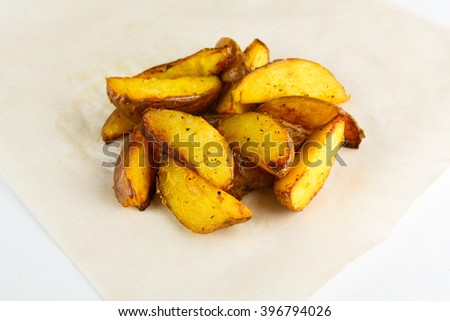 Fried Potato wedges. Natural and organic food from farm. Delicious crispy baked potato wedges closeup at white background. Roasted potato wedges. Closeup at white plate background. Horizontal image - stock photo