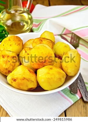 Fried potatoes in a white plate on a napkin, parsley, vegetable oil on a wooden boards background - stock photo