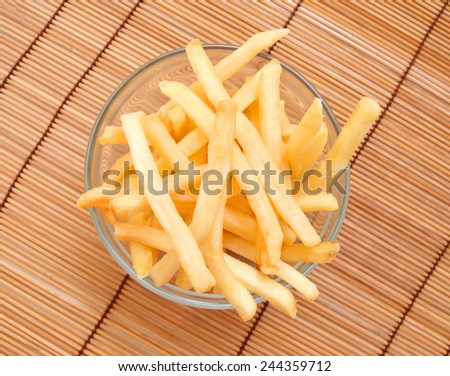fried potatoes in glass bowl on bamboo mat