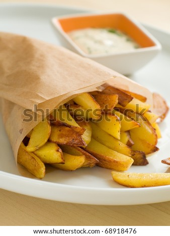 Fried potatoes with sauce on plate - stock photo