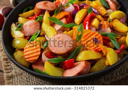 Fried potatoes with vegetables and sausages - stock photo
