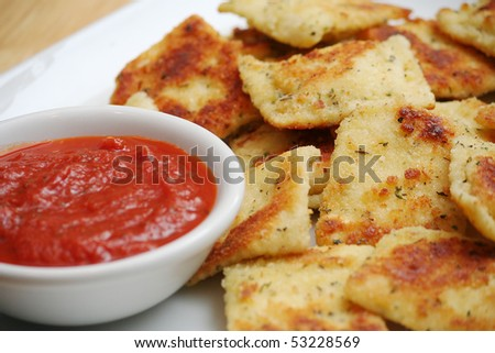 Fried Ravioli on White Plate With a Bowl of Marinara Sauce