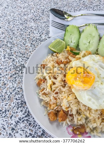 Fried rice and fried egg cucumber on plate with spoon and fork. top view. - stock photo