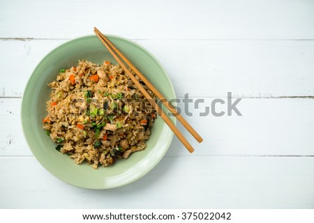 Fried Rice Top View on White Background. Plate of fried rice with chopsticks on the side. This asian inspired recipe uses lots of fresh ingredients like basil, carrots, onions, fried eggs and chicken. - stock photo