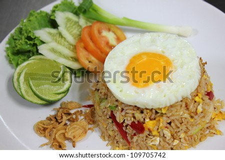 Fried rice with fried egg. Tomato and lemon
