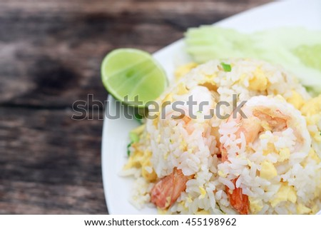 Fried rice with shrimp on the white dish on wooden table