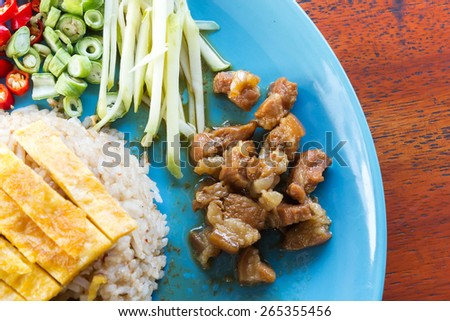 Fried rice with shrimp paste on blue plate. On wooden table. Asian food. Local name is Kao Cluk Ka Pi. - stock photo