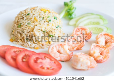 fried rice with shrimps on wood background