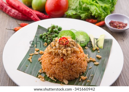fried rice with soy sauce and tomato paste. Served with lettuce, red tomato, green tomato, red chilli, leunca, and young mango - stock photo