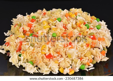 Fried rice with vegetables on black background - stock photo