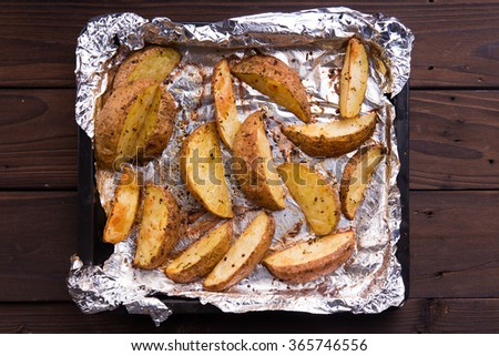 Fried russet potato on tray with aluminium foil on rustic wooden background - stock photo