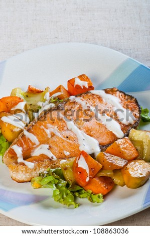 fried salmon on a garden salad and fresh buttered vegetables