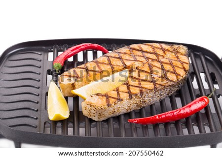 Fried salmon steak on grill. Whole background. - stock photo