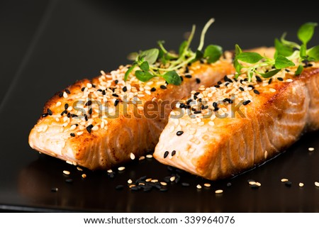 Fried salmon with sesame seeds and herbs on black plate close up - stock photo