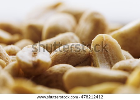 Fried salted peanuts on a white background in a plate. Assorted snack pile of peanuts. Abstract background salted nuts. Roasted salted peanuts in plate, side view. Halves of roasted peanuts.