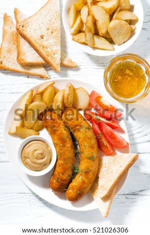 fried sausages with potatoes, mustard and beer, vertical