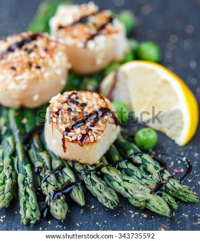 Fried scallop with sesame seeds and balsamic sauce, asparagus, lemon ...