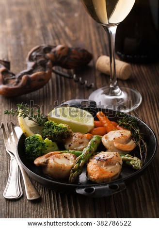 Fried scallops in a sauce with asparagus and broccoli in a frying pan - stock photo