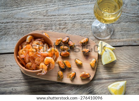 Fried shrimps and mussels with glass of white wine - stock photo