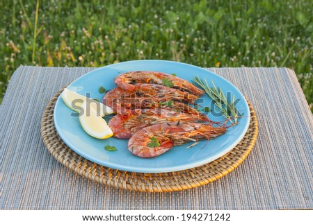 Fried shrimps on a plate with herbs and rosemary, outdoors - stock photo
