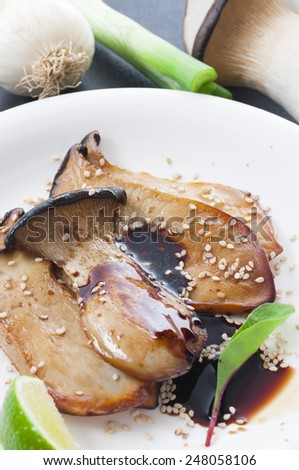 Fried sliced king oyster mushroom with olive oil, soy sauce and sesame seeds. New version. - stock photo