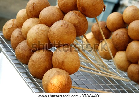 Fried Snack at the market, Thai small Corn Dog in a round ball shape with skewers, popular street food in Thailand - stock photo