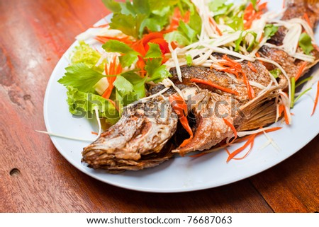 Fried snapper with chili sauce and dressed vegetables on the blue plate place on wood table. - stock photo