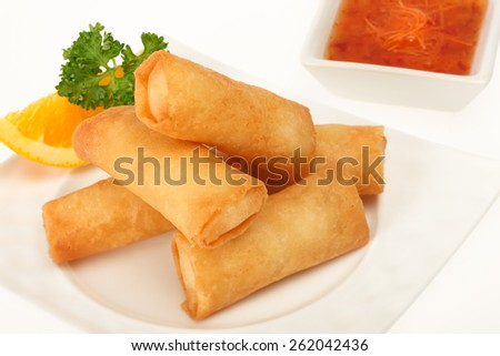 Fried spring rolls on a white plate with spicy sauce and lemon slice studio shot on white background - stock photo