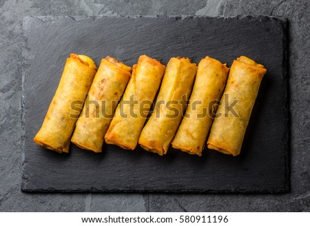 Fried spring rolls on black slate plate on grey stone slate background. Top view