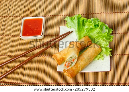 Fried spring rolls, one cut, on a plate with chopsticks served with chili sauce - stock photo