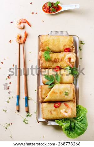 Fried spring rolls with vegetables and shrimps, served with spicy sauce and chopsticks over white wooden background. Top view - stock photo