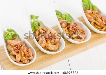Fried Squid Rings - Pan fried squid rings with red pepper. - stock photo