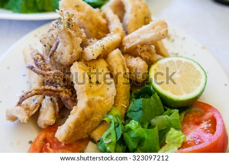 Fried squid rings with lemon  - stock photo
