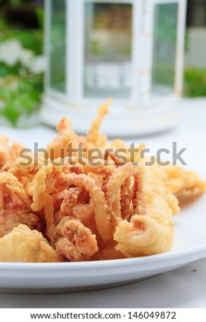 Fried squids at the restaurant table - stock photo