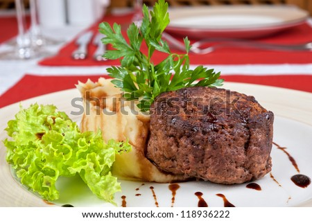 Fried steaks with mashed potatoes, lettuce and greens - stock photo