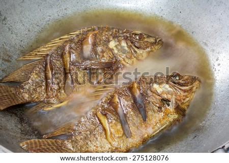 Fried tilapia fish in a frying pan with hot oil - stock photo