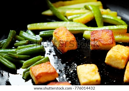 Fried tofu with vegetables on a cast-iron saucepan. A healthy ingredient for cooking vegetarian dietary vegetarian food. Fried tofu on a black background.
