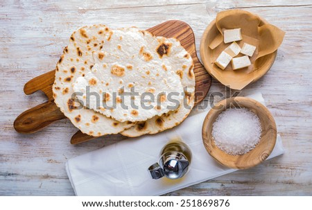 Fried tortilla with cheese on olive wood plate on white background - stock photo