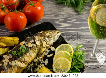 Fried trout with almonds, dill and potato wedges - stock photo