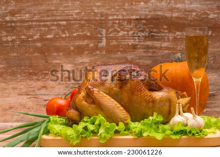 fried turkey with vegetables and glass of wine on a wooden background - stock photo