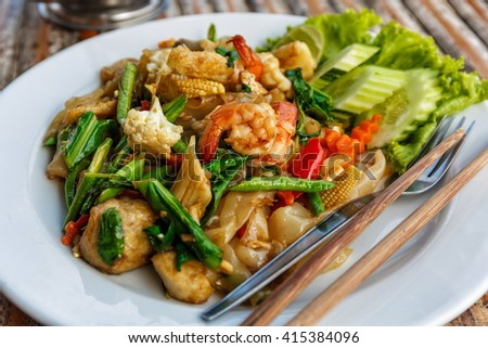 Fried vegetables and seafood in sauce - stock photo