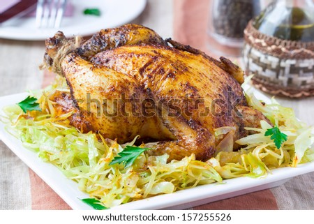 Fried whole chicken with golden crust and garnish of stewed cabbage, for holiday of thanksgiving - stock photo