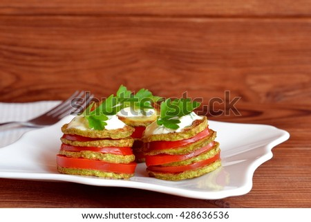 Fried zucchini with fresh tomatoes, yogurt and parsley. Fried zucchini appetizer recipe. Easy vegetable snack. Roasted yellow squash in olive oil.  White napkin, fork, wooden table. Closeup - stock photo