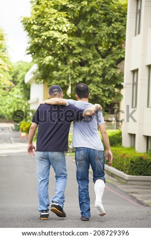 friend helping brothers or patient  to walk without crutches  - stock photo