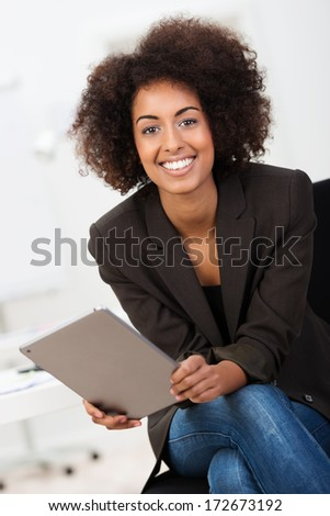 Friendly African American businesswoman with a beautiful smile and afro hairstyle sitting holding a tablet computer looking at the camera - stock photo