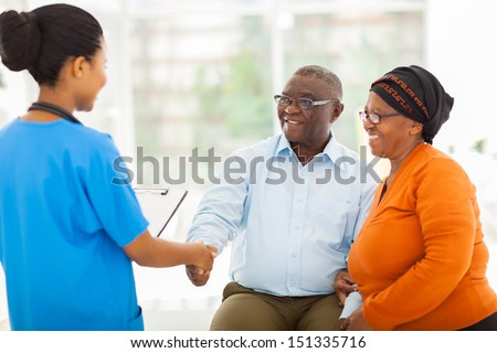 friendly african female nurse greeting senior couple in hospital - stock photo