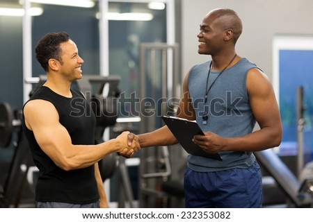 friendly african gym trainer handshaking with mid age client in gym - stock photo